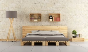 Modern bedroom with pallet bed on brick wall